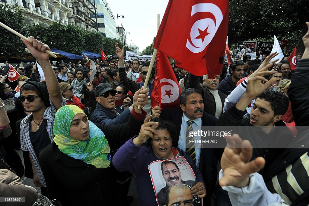 Tunisian people shoot slogans during a demonstration to mark the 40th day of mourning after the death of anti-Islamist opposition leader Chokri Belaid on March 16, 2013 on the Habib Bourguiba Avenue in Tunis. Belaid was gunned down outside his Tunis home on February 6, 2013 with the broad daylight killing sparking clashes between protesters and police and prompting the largest anti-government demonstrations since the revolution. AFP PHOTO / FETHI BELAID