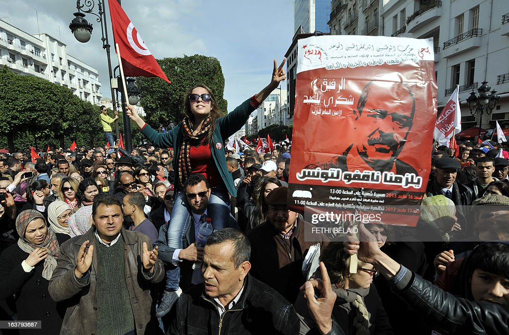 Tunisian people shoot slogans during a demonstration to mark the 40th day of mourning after the death of anti-Islamist opposition leader Chokri Belaid (featured on poster) on March 16, 2013 on the Habib Bourguiba Avenue in Tunis. Belaid was gunned down outside his Tunis home on February 6, 2013 with the broad daylight killing sparking clashes between protesters and police and prompting the largest anti-government demonstrations since the revolution.