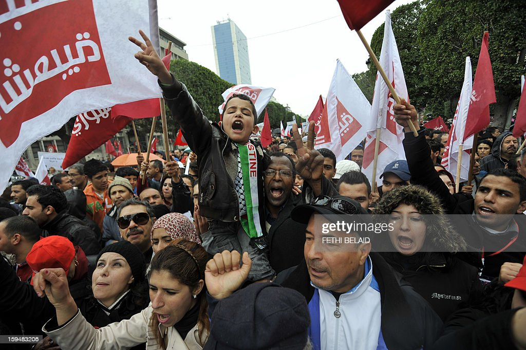Tunisian people shout slogans during a gathering as part of the festivities marking the second anniversary of the uprising that ousted long-time dictator Zine El Abidine Ben Ali on January 14, 2013 in Tunis. Tunisians marked two years since the revolution amid a climate of uncertainty marked by social tension, a weak economy, threats from jihadists and a political impasse. AFP PHOTO / FETHI BELAID