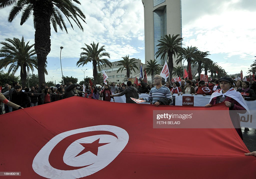 Tunisian people wave a giant national flag as part of the festivities marking the second anniversary of the uprising that ousted long-time dictator Zine El Abidine Ben Ali on January 14, 2013 in Tunis. Tunisians marked two years since the revolution amid a climate of uncertainty marked by social tension, a weak economy, threats from jihadists and a political impasse.