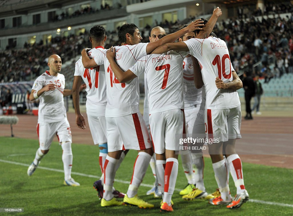 Tunisian players hug their teammate Oussama Darragi (R) after scoring against Serra Leone on March 23, 2013 in Rades stadium during their 2014 World Cup qualifying football match. Tunisia won 2-1.