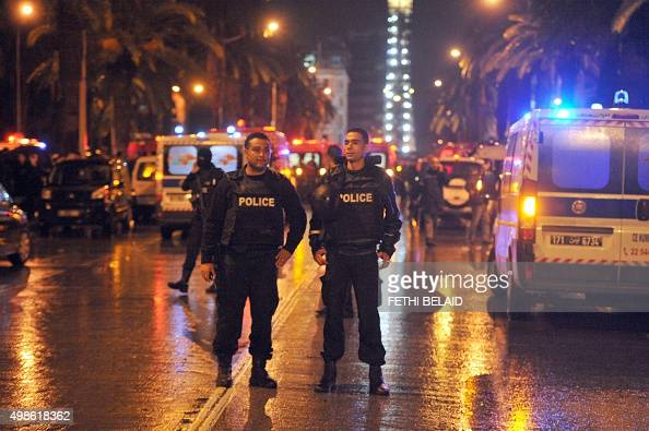 Tunisian police block the road leading to the site of an explosion on a bus transporting Tunisia's presidential guard in central Tunis on November 24...