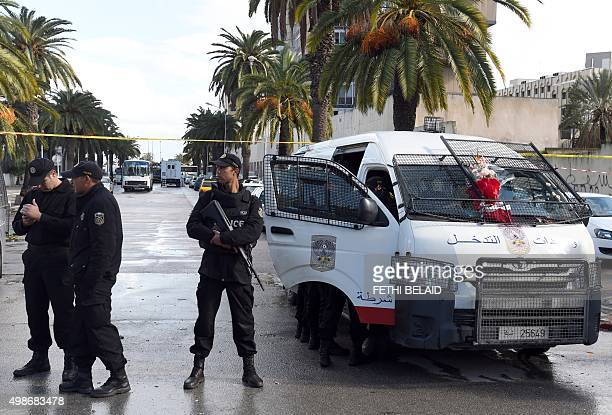 Tunisian police stand guard at the site the day after a bomb attack on a bus which was transporting Tunisia's presidential guards in central Tunis on...