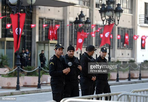 Tunisian police stand guard in front of the interior ministry during a rally on January 14 2016 in the Habib Bourguiba Avenue in the capital Tunis to...