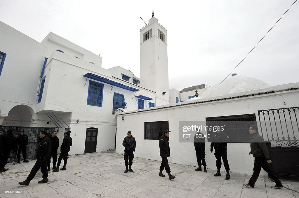 Tunisian police stand guard outside the Sidi Bou Said mausoleum in Tunisia on January 24, 2013. The renovation project of the recently torched mausoleum is mid-way through, as it was prepared for a modest reopening to welcome visitors commemorating the birth of Prophet Mohammed, known in Arabic as 'al-Mawlid al-Nabawi'. In the 35th such attack in seven months, unidentified assailants hurled Molotov cocktails at the Sidi Ahmed Uwerfelli shrine in Akuda, 140 kilometres (85 miles) south of Tunis.