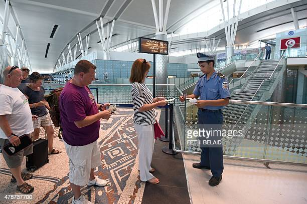 A Tunisian policeman checks tickets of British tourists leaving the country at the Enfidha International airport on June 27 in the aftermath of a...