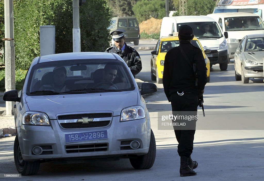 Tunisian policemen check a car at a checkpoint after security forces were deployed on roads leading to the Douar Hicher suburb of Manouba, a Salafist hotspot near Tunis, on December 31, 2012. Tunisian police raided the working class suburb of the capital in a hunt for suspected Salafist arms caches on the previous day, sparking a firefight in which a woman was killed, the interior ministry said.