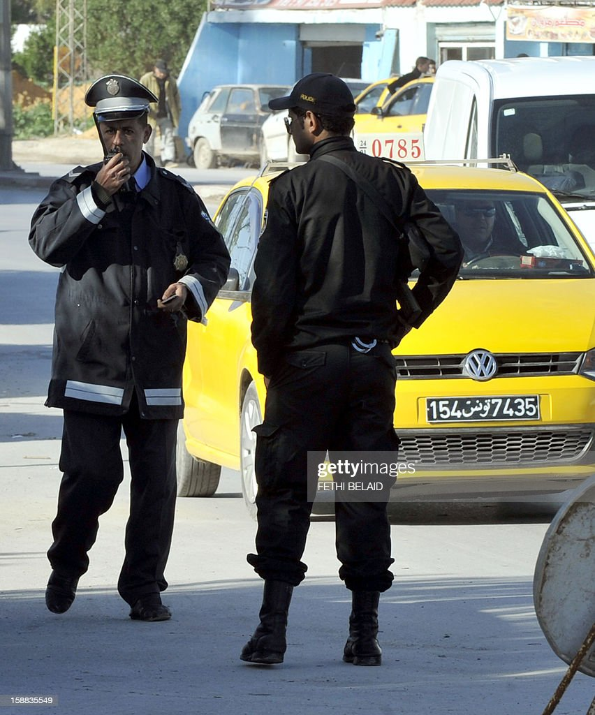 Tunisian policemen man a checkpoint after security forces were deployed on roads leading to the Douar Hicher suburb of Manouba, a Salafist hotspot near Tunis, on December 31, 2012. Tunisian police raided the working class suburb of the capital in a hunt for suspected Salafist arms caches on the previous day, sparking a firefight in which a woman was killed, the interior ministry said.