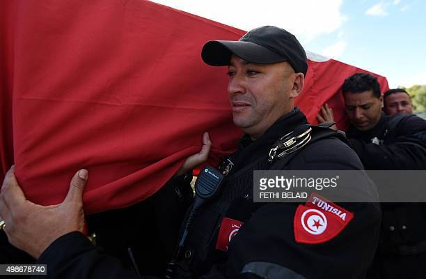 Tunisian policemen mourn as they carry the coffin of a member of the presidential guards who was killed in a bomb blast on a bus in central Tunis the...