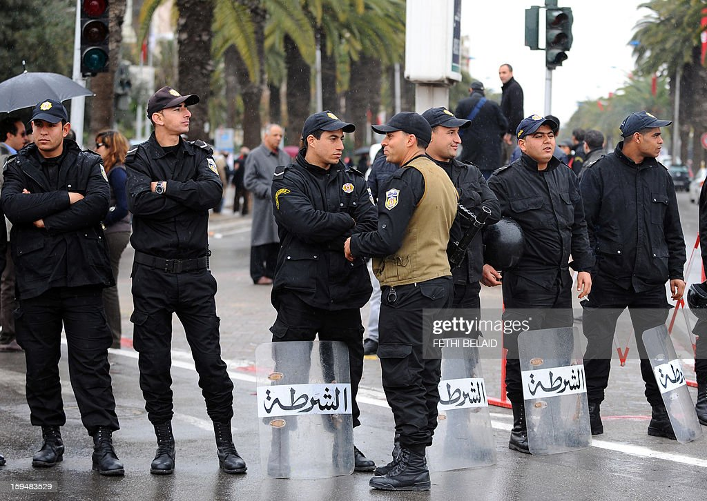 Tunisian policemen stand guard during a gathering as part of the festivities marking the second anniversary of the uprising that ousted long-time dictator Zine El Abidine Ben Ali on January 14, 2013 in Tunis. Tunisians marked two years since the revolution amid a climate of uncertainty marked by social tension, a weak economy, threats from jihadists and a political impasse.