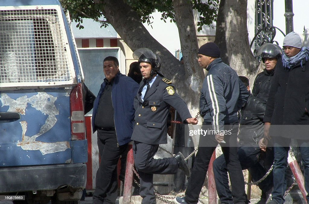 Tunisian policemen stand guard over protesters who demonstrate against the killing of lawyer and leftist opposition leader Chokri Belaid outside the governor's office in the central Tunisian town of Gafsa on February 7, 2013. The protesters, who were observing a symbolic funeral for Belaid, threw petrol bombs at the police, who fired large quantities of tear gas in a bid to disperse them. AFP PHOTO / STR