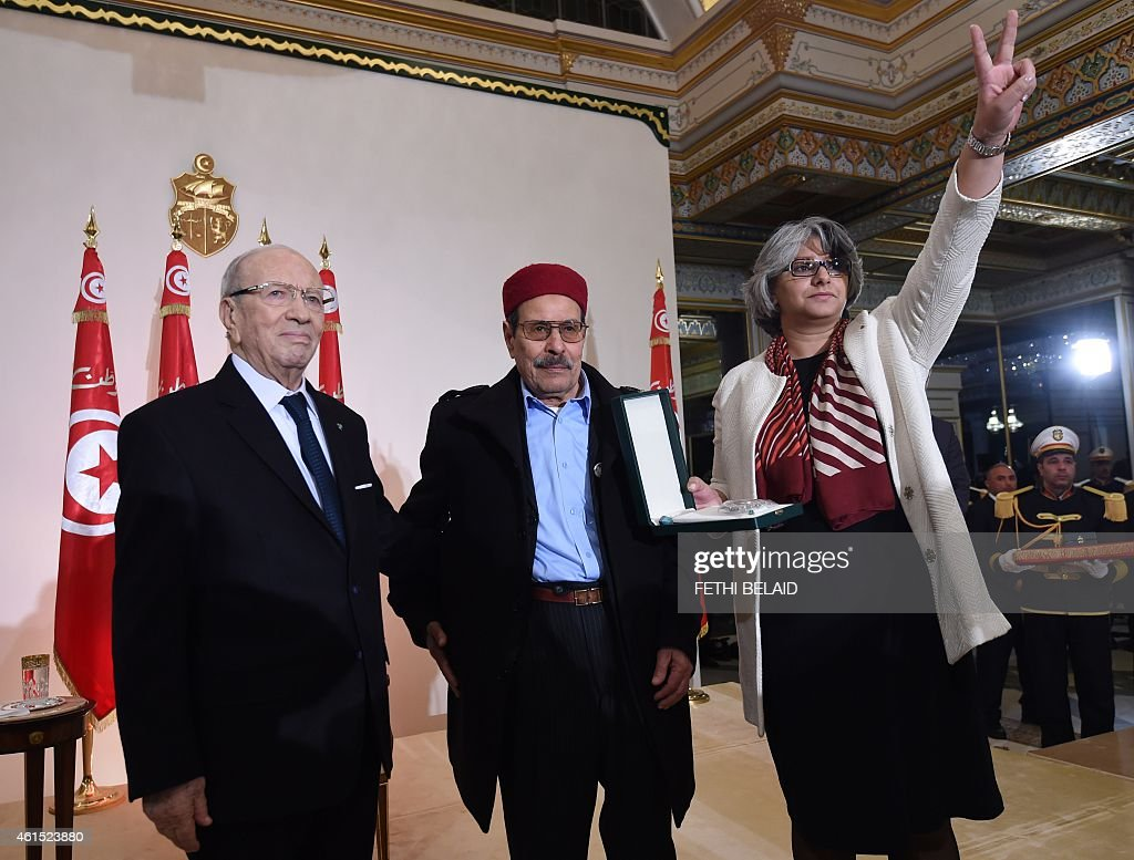 Tunisian President Beji Caid Essebsi (C) honours Besma Khalfaoui (R), the widow of slain Tunisian opposition leader Chokri Belaid, and his father Salah Belaid (C) during an event in Tunis on January 14, 2015, marking the fourth anniversary of the ousting of Tunisia's longtime ruler Zine el Abidine Ben Ali, that sparked the Arab Spring uprisings. On January 14 2011, under massive popular pressure over unemployment and inflation, Ben Ali fled to Saudi Arabia with his family after 23 years in power. AFP PHOTO/ FETHI BELAID