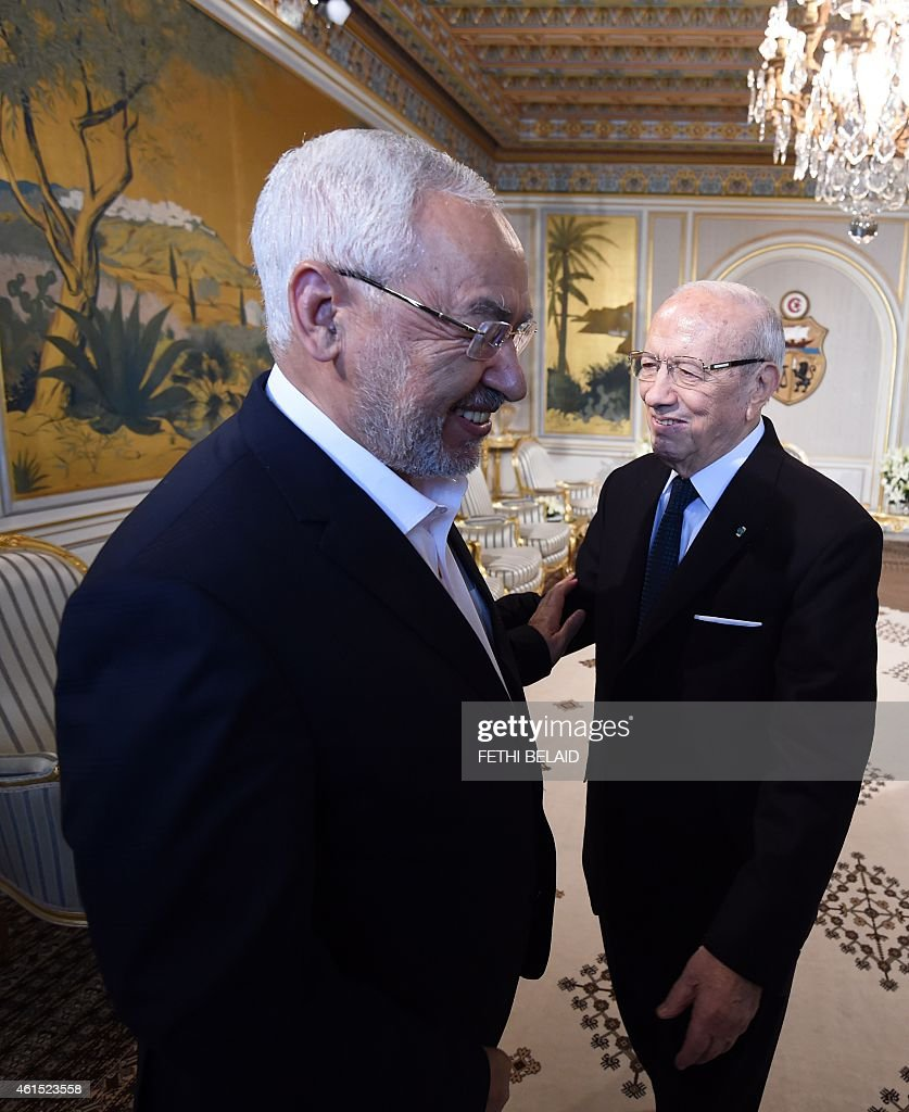 Tunisian President Beji Ceid Essebsi (R) greets Ennahdha Islamist party Leader Rached Ghannouchi during an event in Tunis on January 14, 2015, marking the fourth anniversary of the ousting of Tunisia's longtime ruler Zine el Abidine Ben Ali, that sparked the Arab Spring uprisings. On January 14 2011, under massive popular pressure over unemployment and inflation, Ben Ali fled to Saudi Arabia with his family after 23 years in power. AFP PHOTO/ FETHI BELAID