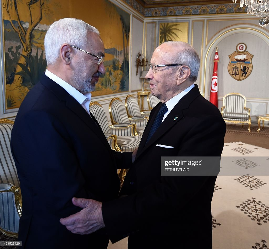 Tunisian President Beji Ceid Essebsi (R) shakes hands with Ennahdha Islamist party Leader Rached Ghannouchi during an event in Tunis on January 14, 2015, marking the fourth anniversary of the ousting of Tunisia's longtime ruler Zine el Abidine Ben Ali, that sparked the Arab Spring uprisings. On January 14 2011, under massive popular pressure over unemployment and inflation, Ben Ali fled to Saudi Arabia with his family after 23 years in power. AFP PHOTO/ FETHI BELAID