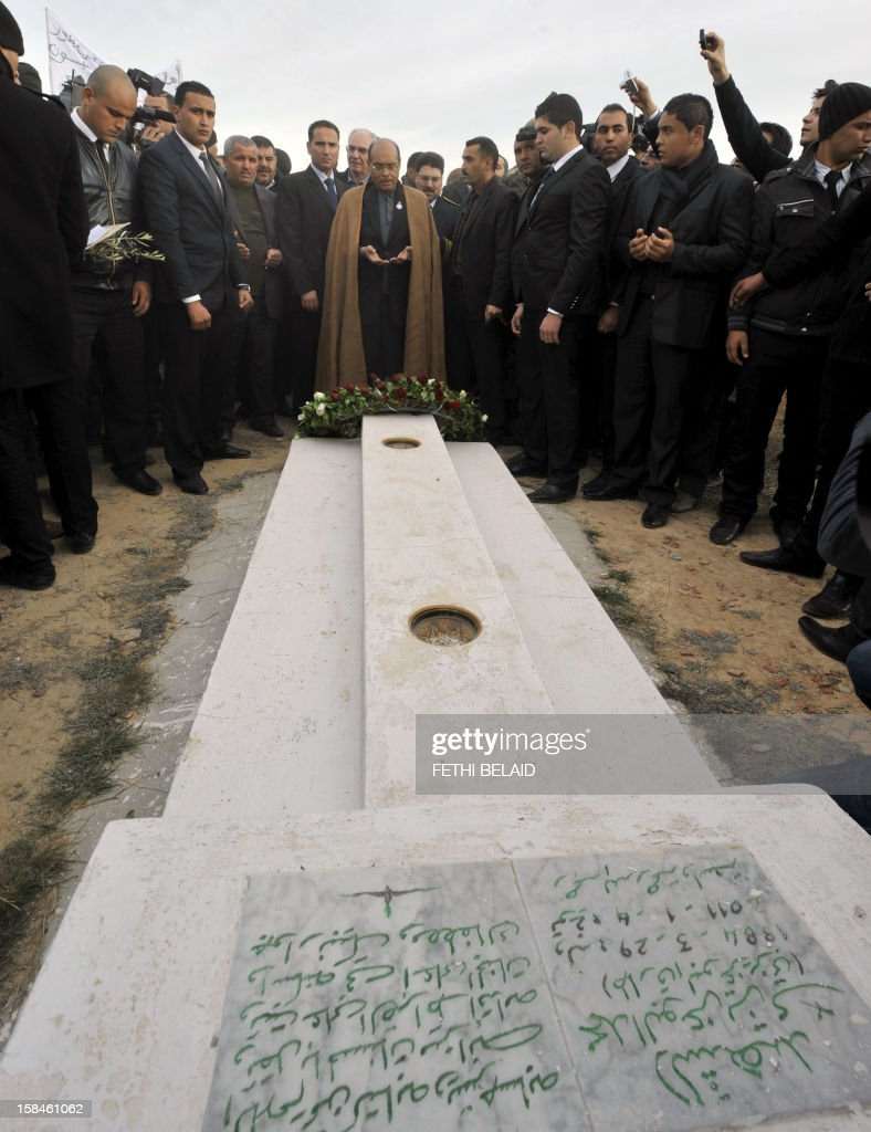 Tunisian President Moncef Marzouki (C) prays at the mausoleum of Mohamed Bouazizi, the young fruit and vegetable seller whose self-immolation kicked off the Arab Spring in the central town of Sidi Bouzid on December 17, 2012, as Tunisia marks the second anniversary of the start of the revolution. Marzouki was heckled when he visited the grave. AFP PHOTO / FETHI BELAID