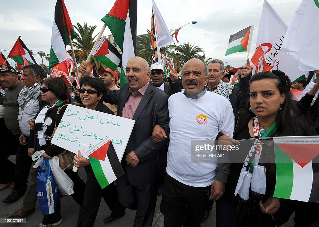 Tunisian President of the Human Rights League of Tunisia (LTDH), Abdessatter Moussa (C) holds Palestinian flags during a global anti-capitalist demonstration to demand justice at the closing of the World Social Forum (WSF) on March 30, 2013 in Tunis.