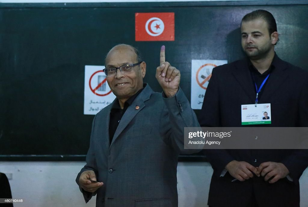 Tunisian presidential candidate Moncef Marzouki demonstrates his painted finger after casting his vote at Sidi el Kantaoui school during the second round of Tunisia's presidential election on December 21,2014.