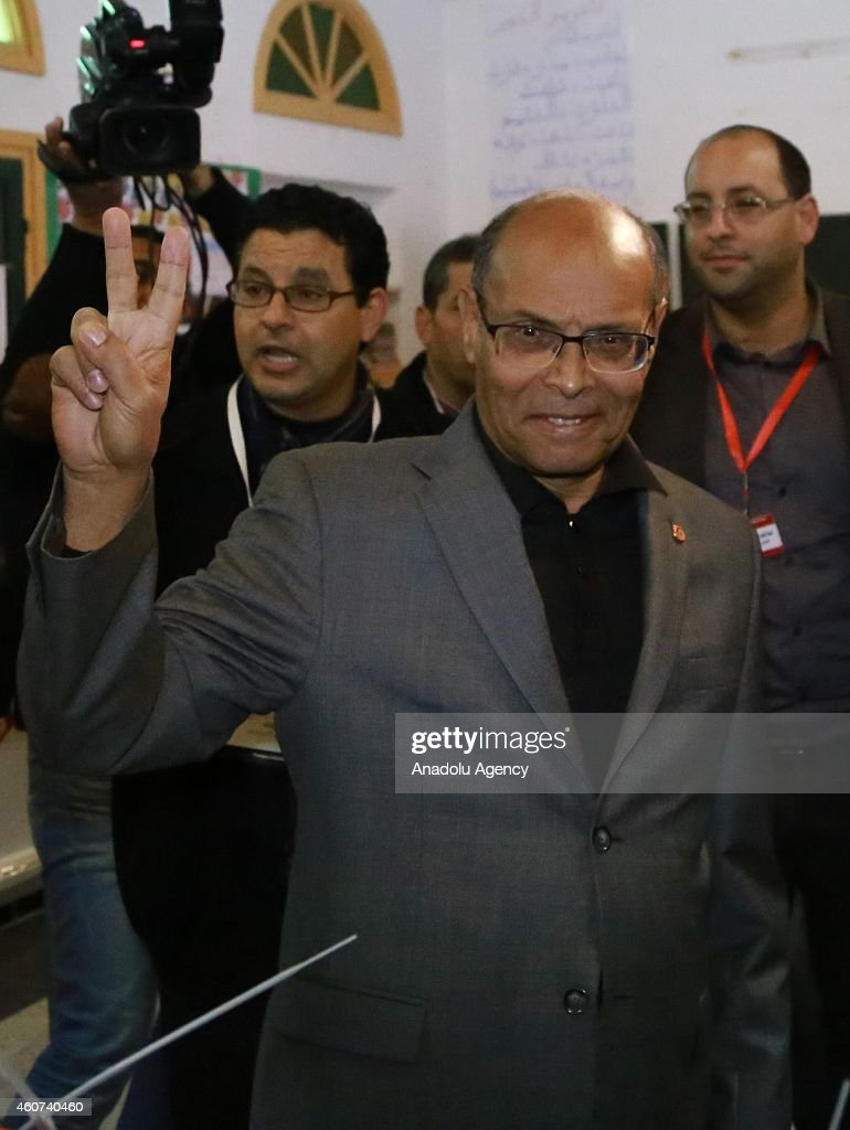 Tunisian presidential candidate Moncef Marzouki flashes victory sign after casting his vote at Sidi el Kantaoui school during the second round of Tunisia's presidential election on December 21,2014.