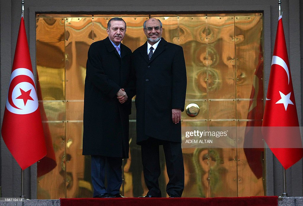 Tunisian Prime Minister Hamadi Jebali (R) and his Turkish counterpart Recep Tayyip Erdogan shake hands during a welcoming ceremony in Ankara on December 25, 2012. AFP PHOTO/ADEM ALTAN