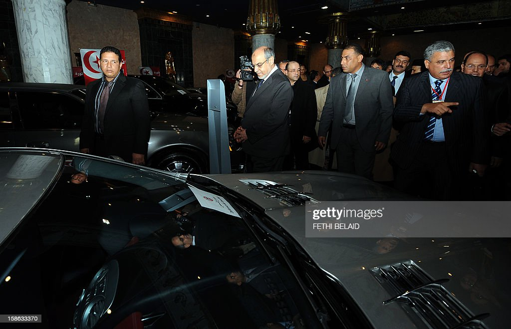 Tunisian Prime Minister Hamadi Jebali (C) walks past luxury cars that once belonged to ousted Tunisian dictator Zine El Abidine Ben Ali at an auction in the Tunis suburb of Gammarth on December 22, 2012. Jebali kicked off viewing of thousands of luxury items once owned by the ousted leader and his family on the eve of a public auction, in a bid to raise millions of euros for government coffers.