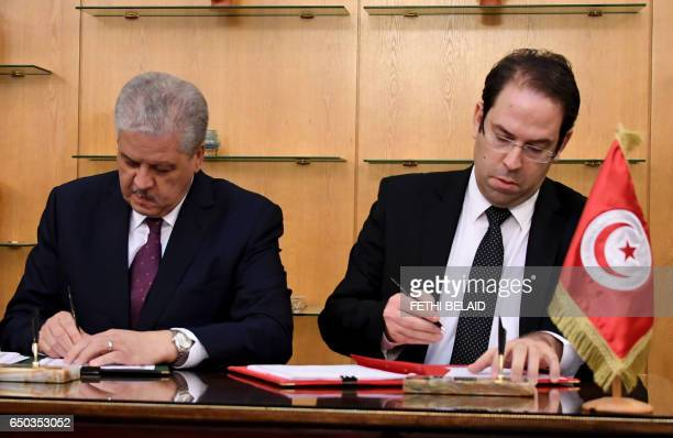 Tunisian Prime Minister Youssef Chahed exchanges documents with his Algerian counterpart Abdelmalek Sellal after signing the cooperation...
