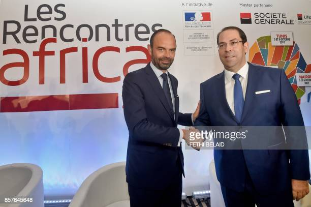 Tunisian Prime Minister Youssef Chahed shakes hands with his French counterpart Edouard Philippe during a FranceAfrica economic meeting in Tunis on...