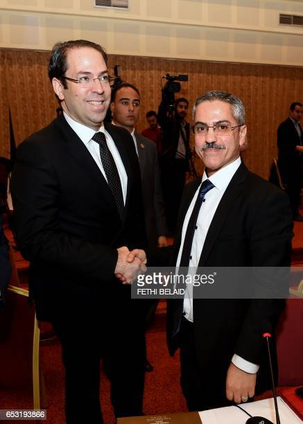 Tunisian Prime minister Youssef Chahed shakes hands with the head of the Tunisian ISIE elections body Chafik Sarsar during a meeting in Gammarth near...