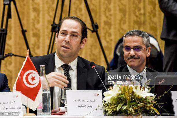 Tunisian Prime minister Youssef Chahed sits with the head of the Tunisian ISIE elections body Chafik Sarsar during a meeting in Gammarth near the...