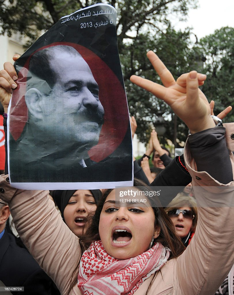 A Tunisian protester flashes the sign of victory holding a poster featuring killed opposition leader Chokri Belaid during a demonstration on February 23, 2013 on the Habib Bourguiba Avenue in Tunis. Hundreds of demonstrators marched to protest against the Islamist party Ennahda in power, and demanded that Belaid's killers be found. AFP PHOTO / FETHI BELAID