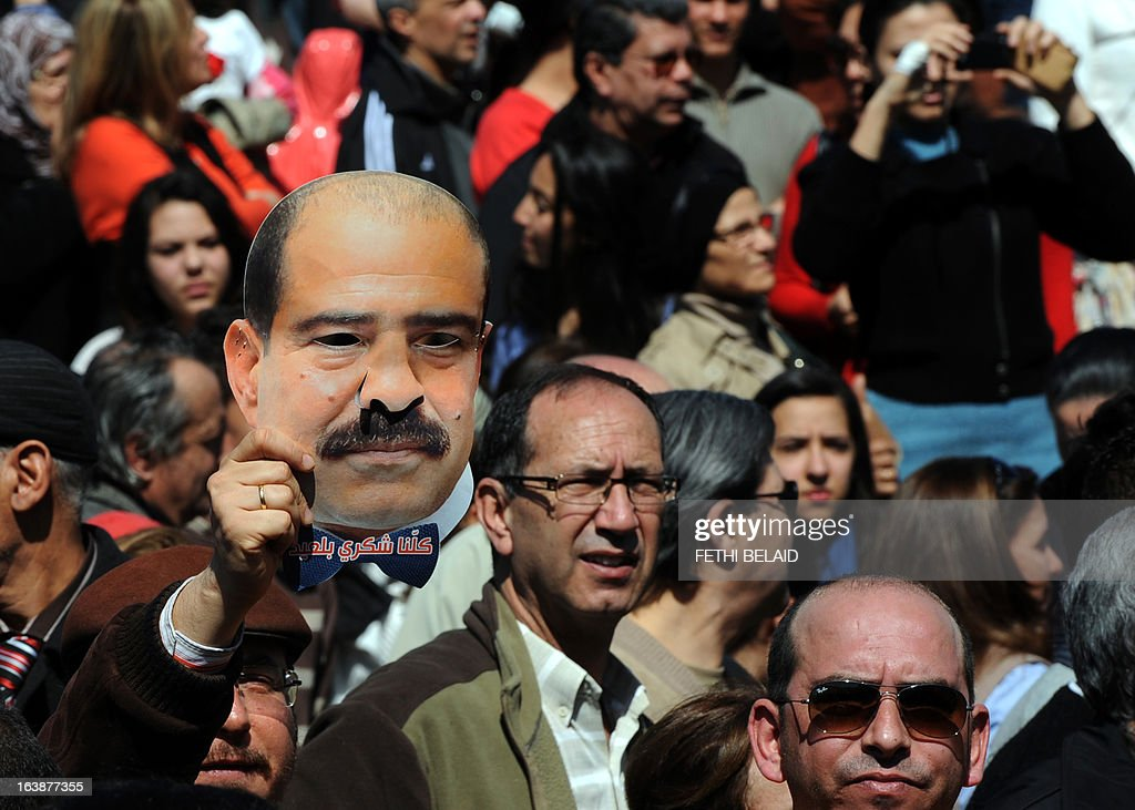 A Tunisian protester holds a mask of slain opposition leader Chokri Belaid as people mark 40 days since his killing outside his house in Tunis on March 17, 2013. Belaid, a critic of the ruling Islamists whose death plunged Tunisia into turmoil, was gunned down outside his home on February 6 in a killing blamed by the authorities on radical Islamists, denying any involvement. Several arrests in the case have been made, but the suspected killer remains at large.