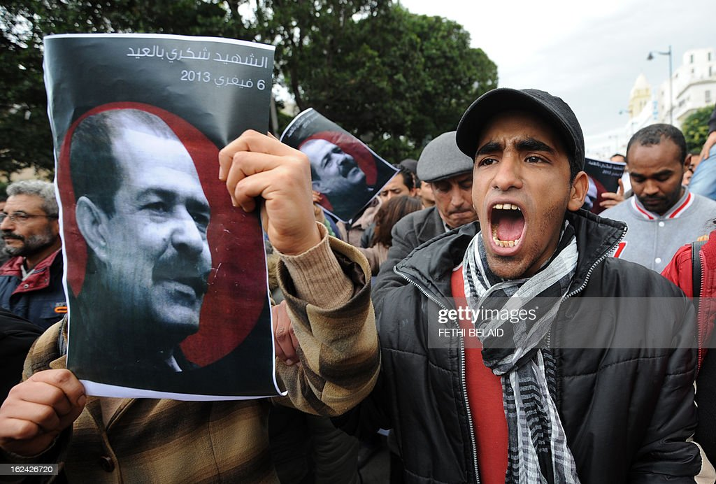 A Tunisian protester holds a placard featuring killed opposition leader Chokri Belaid during a demonstration on February 23, 2013 on the Habib Bourguiba Avenue in Tunis. Hundreds of demonstrators marched to protest against the Islamist party Ennahda in power, and demanded that Belaid's killers be found.