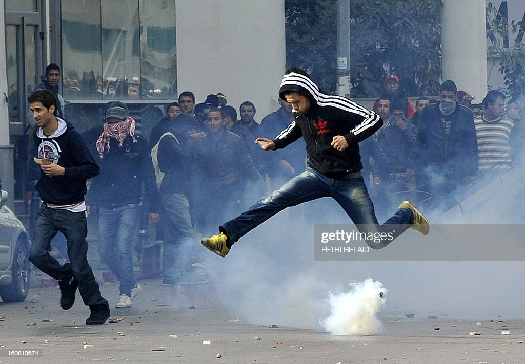 A Tunisian protester jumps amid smoke after police fired tear gas during a rallye outside the Interior ministry to protest after Tunisian opposition leader and outspoken government critic Chokri Belaid was shot dead with three bullets fired from close range, on February 6, 2013 in Tunis. The protesters, who massed on Habib Bourguiba Avenue, epicentre of the 2011 uprising that ousted ex-dictator Zine El Abidine Ben Ali, pelted the police with bottles and the police responded by firing tear gas, chasing the protesters and beating them with batons.