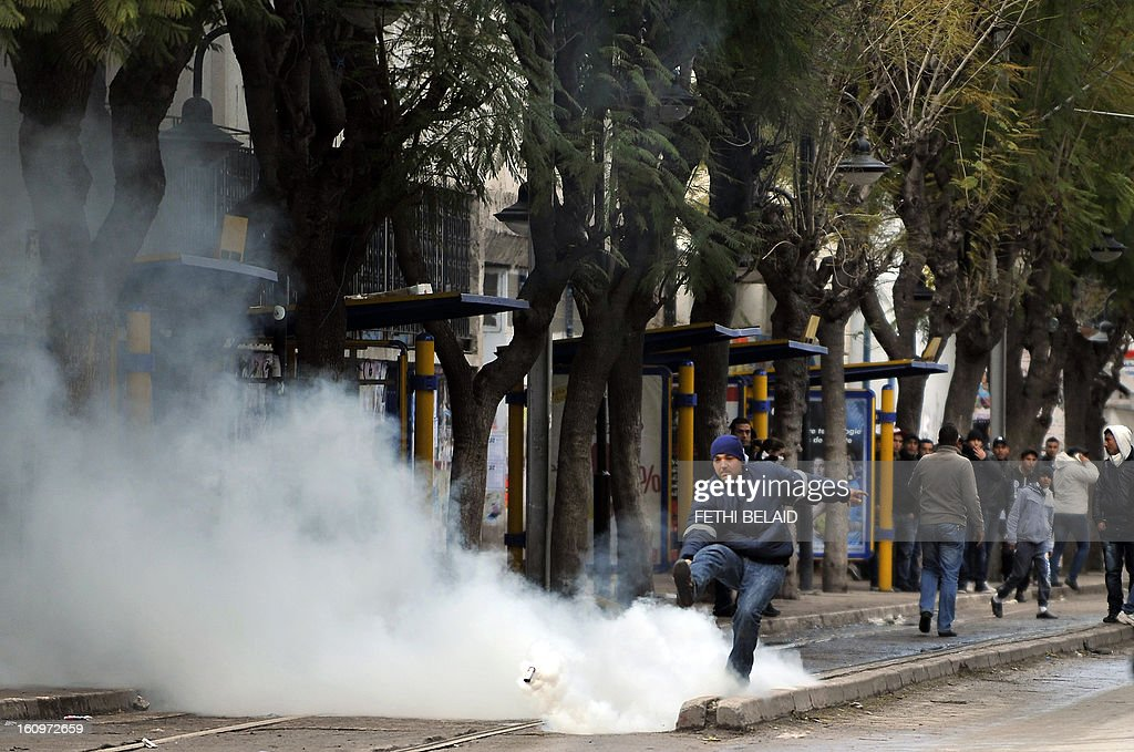 A Tunisian protester kicks a tear gas canister fired by policemen during clashes following the funeral of assassinated opposition leader Chokri Belaid in Tunis on February 8, 2013. Tunisian police fired tear gas and clashed with protesters as tens of thousands joined the funeral of Belaid whose murder plunged the country into new post-revolt turmoil. AFP PHOTO/FETHI BELAID