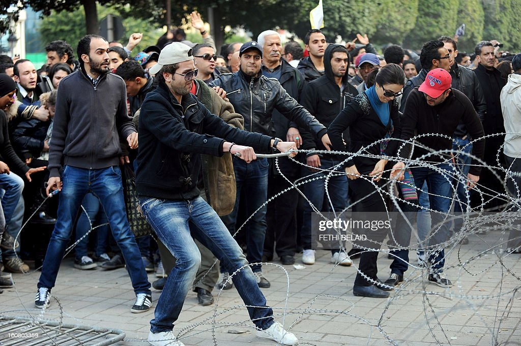 A Tunisian protester removes barbed wire during a rallye outside the Interior ministry to protest after Tunisian opposition leader and outspoken government critic Chokri Belaid was shot dead with three bullets fired from close range, on February 6, 2013 n Tunis. The protesters, who massed on Habib Bourguiba Avenue, epicentre of the 2011 uprising that ousted ex-dictator Zine El Abidine Ben Ali, pelted the police with bottles and the police responded by firing tear gas, chasing the protesters and beating them with batons.