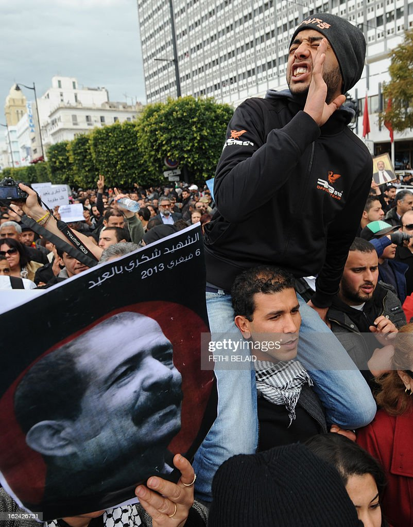 A Tunisian protester shouts slogans near a poster featuring killed opposition leader Chokri Belaid during a demonstration on February 23, 2013 on the Habib Bourguiba Avenue in Tunis. Hundreds of demonstrators marched to protest against the Islamist party Ennahda in power, and demanded that Belaid's killers be found.