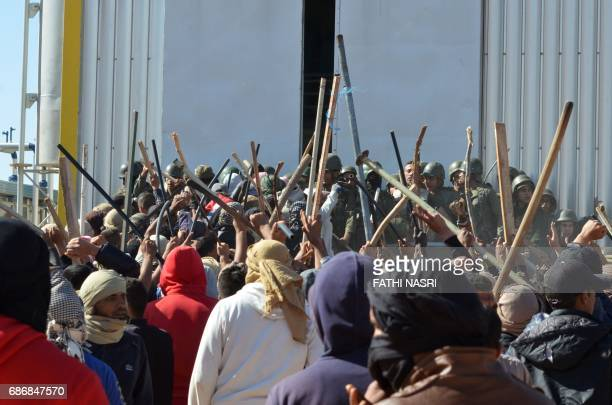 Tunisian protesters comfront security forces outside the El Kamour oil and gas pumping station in the southern state of Tataouine on May 22 during a...