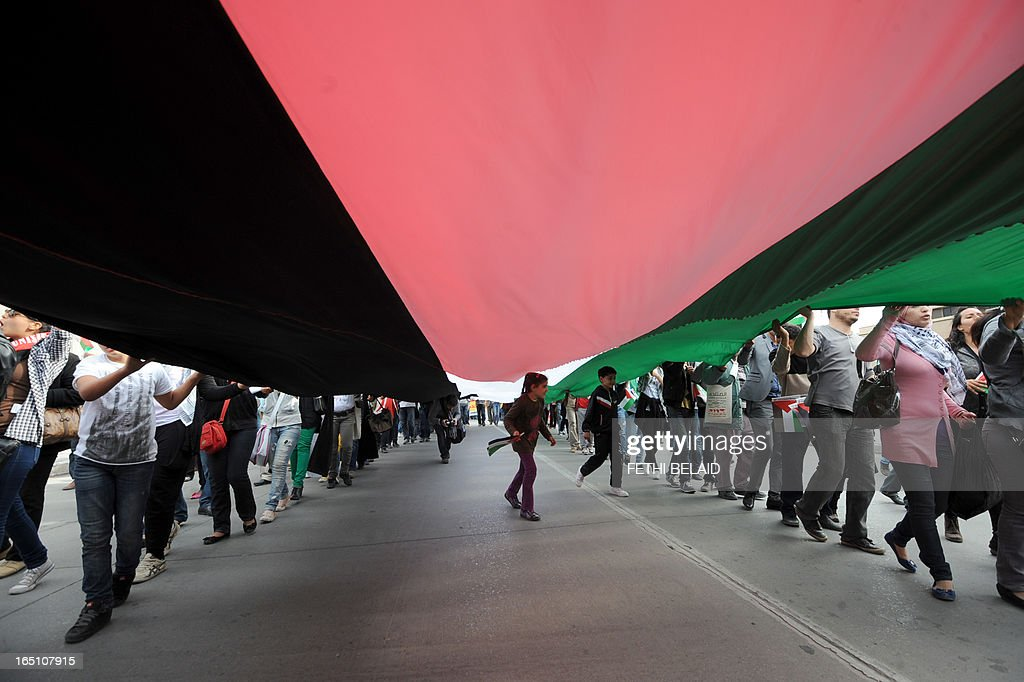 Tunisian protesters deploy a giant Palestinian flag during a global anti-capitalist demonstration to demand justice at the closing of the World Social Forum (WSF) on March 30, 2013 in Tunis. Tunisia must find a new economic model to raise the roughly 20 percent of its people living in poverty from their quagmire, President Moncef Marzouki said on Saturday. AFP PHOTO / FETHI BELAID