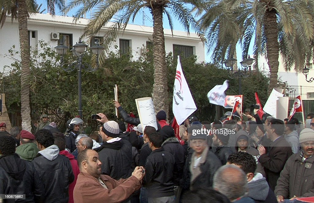 Tunisian protesters gather outside the governor's office in the central Tunisian town of Gafsa during a demonstration to protest against the killing of lawyer and leftist opposition leader Chokri Belaid on February 7, 2013. The protesters, who were observing a symbolic funeral for Belaid, threw petrol bombs at the police, who fired large quantities of tear gas in a bid to disperse them.