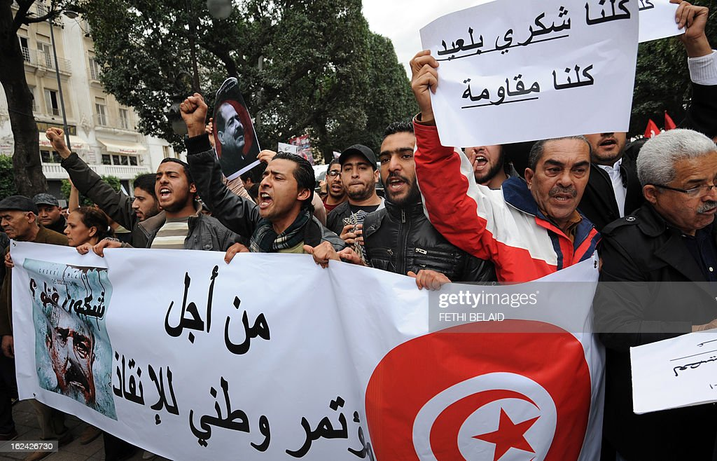 Tunisian protesters hold a banner shouting slogans during a demonstration on February 23, 2013 on the Habib Bourguiba Avenue in Tunis. Hundreds of demonstrators marched to protest against the Islamist party Ennahda in power, and demanded that opposition leader Chokri Belaid's killers be found. The banner at bottom reads in Arabic 'For a national conference for salvation'. AFP PHOTO / FETHI BELAID