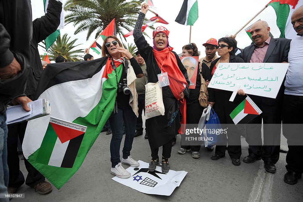 Tunisian protesters hold Palestinian flags and placards during a global anti-capitalist demonstration to demand justice at the closing of the World Social Forum (WSF) on March 30, 2013 in Tunis. Tunisia must find a new economic model to raise the roughly 20 percent of its people living in poverty from their quagmire, President Moncef Marzouki said on Saturday.