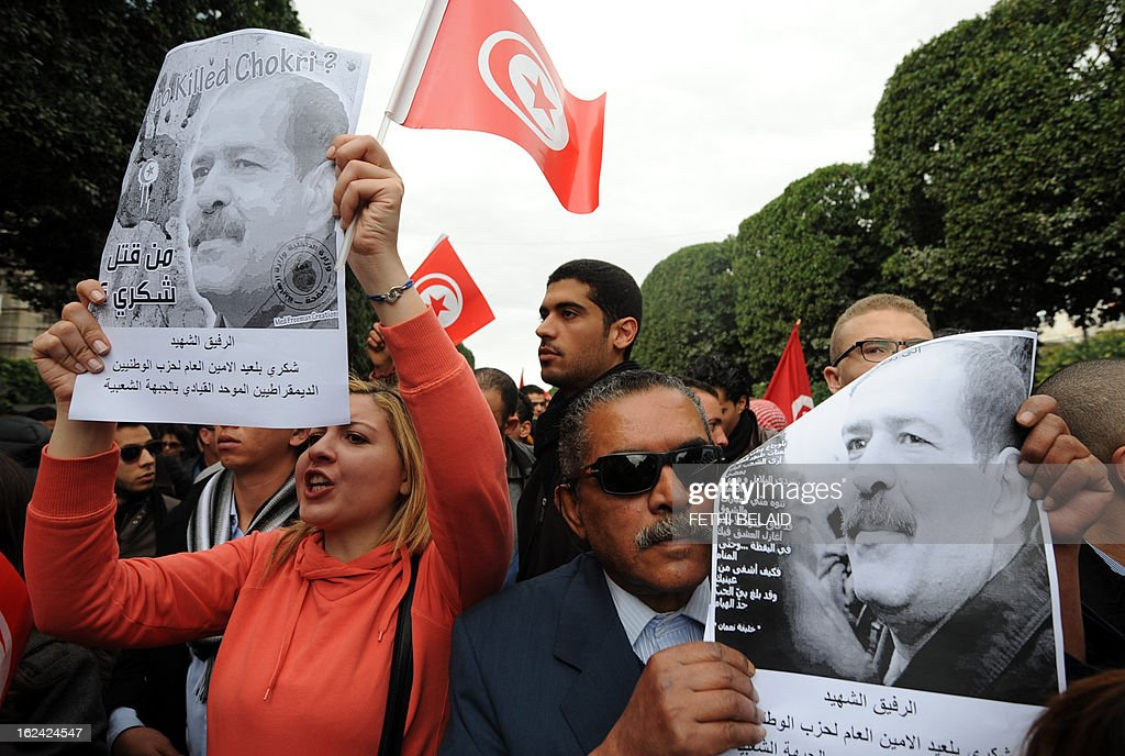 Tunisian protesters hold placards featuring killed opposition leader Chokri Belaid during a demonstration on February 23, 2013 on the Habib Bourguiba Avenue in Tunis. Hundreds of demonstrators marched to protest against the Islamist party Ennahda in power, and demanded that Belaid's killers be found.