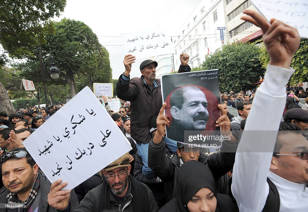 Tunisian protesters hold placards shouting slogans during a demonstration on February 23, 2013 on the Habib Bourguiba Avenue in Tunis. Hundreds of demonstrators marched to protest against the Islamist party Ennahda in power, and demand that opposition leader Chokri Belaid's killers be found.