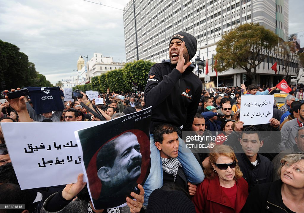 Tunisian protesters hold placards shouting slogans during a demonstration on February 23, 2013 on the Habib Bourguiba Avenue in Tunis. Hundreds of demonstrators marched to protest against the Islamist party Ennahda in power, and demand that opposition leader Chokri Belaid's (featured on the poster) killers be found. AFP PHOTO / FETHI BELAID