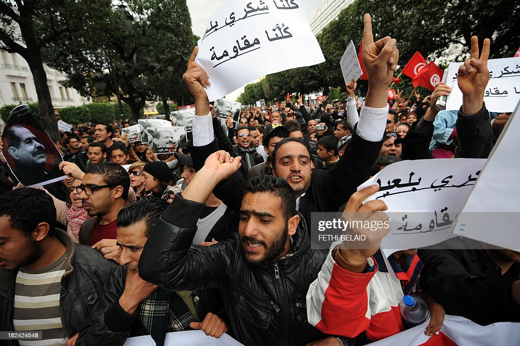 Tunisian protesters hold placards shouting slogans during a demonstration on February 23, 2013 on the Habib Bourguiba Avenue in Tunis. Hundreds of demonstrators marched to protest against the Islamist party Ennahda in power, and demanded that opposition leader Chokri Belaid's killers be found.