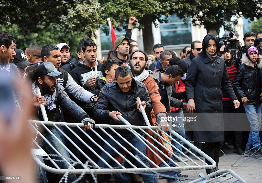 Tunisian protesters remove fences during a rallye outside the Interior ministry to protest after Tunisian opposition leader and outspoken government critic Chokri Belaid was shot dead with three bullets fired from close range, on February 6, 2013. The protesters, who massed on Habib Bourguiba Avenue, epicentre of the 2011 uprising that ousted ex-dictator Zine El Abidine Ben Ali, pelted the police with bottles and the police responded by firing tear gas, chasing the protesters and beating them with batons.