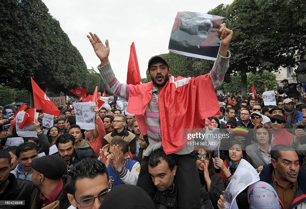 Tunisian protesters shout slogans during a demonstration on February 23, 2013 on the Habib Bourguiba Avenue in Tunis. Hundreds of demonstrators marched to protest against the Islamist party Ennahda in power, and demanded that opposition leader Chokri Belaid's killers be found. Belaid is featured on the poster.