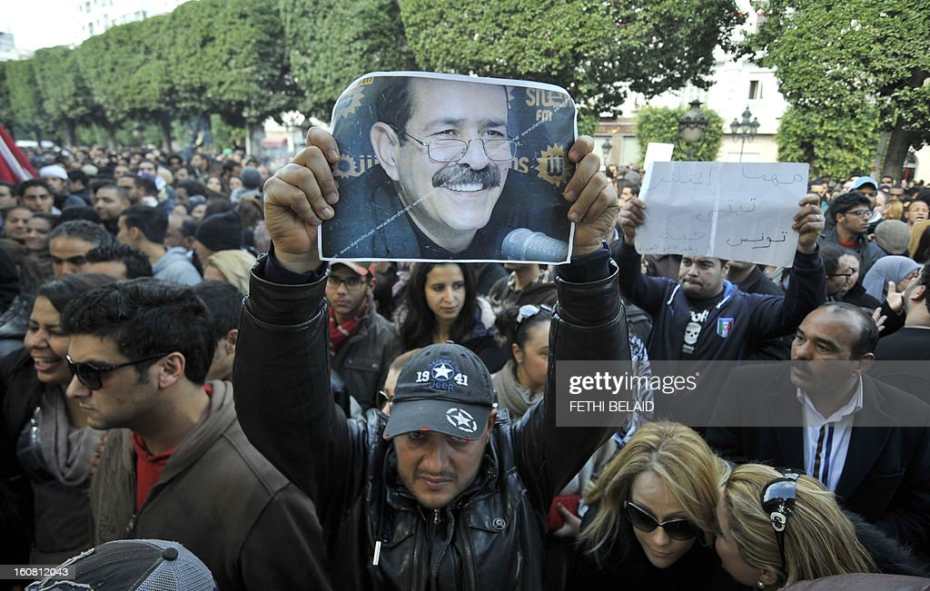 Tunisian protesters shout slogans during a rally outside the Interior Ministry to protest against the assassination of Tunisian opposition leader and outspoken government critic Chokri Belaid (poster) on February 6, 2013, in Tunis. The protesters, who massed on Habib Bourguiba Avenue, epicentre of the 2011 uprising that ousted former dictator Zine El Abidine Ben Ali, pelted the police with bottles and the police responded by firing tear gas, chasing the protesters and beating them with batons. AFP PHOTO / FETHI BELAID