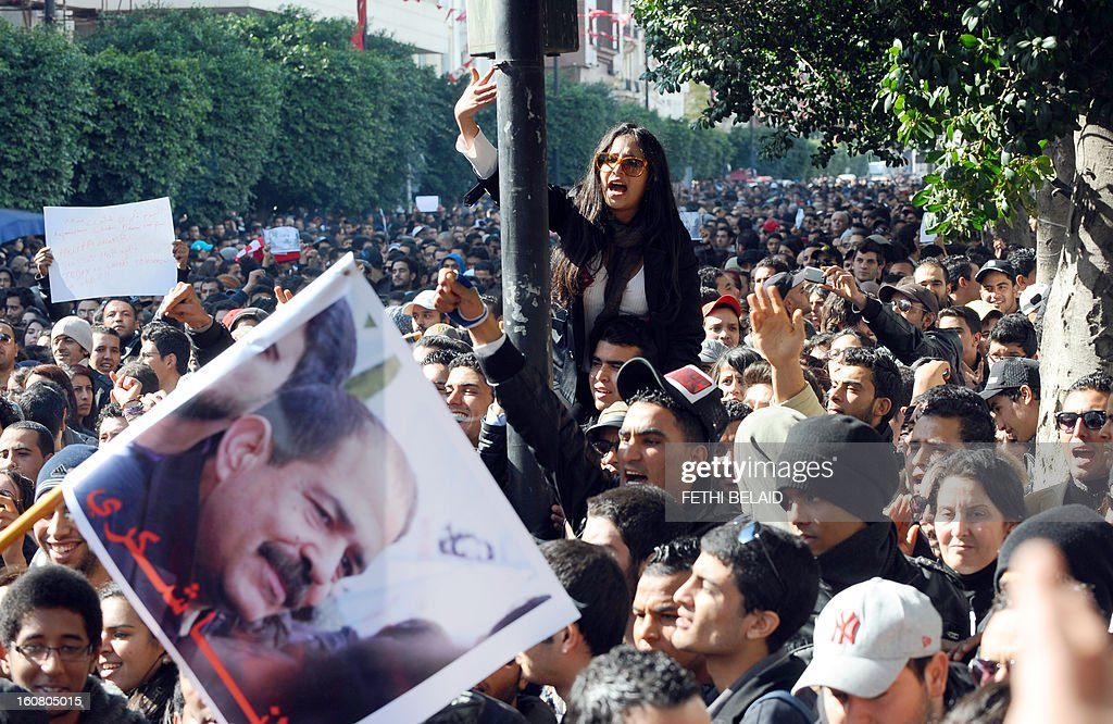 Tunisian protesters shout slogans during a rallye outside the Interior ministry to protest after Tunisian opposition leader and outspoken government critic Chokri Belaid (featured on the poster) was shot dead on February 6, 2013 in Tunis. The protesters, who massed on Habib Bourguiba Avenue, epicentre of the 2011 uprising that ousted ex-dictator Zine El Abidine Ben Ali, pelted the police with bottles and the police responded by firing tear gas, chasing the protesters and beating them with batons. AFP PHOTO / FETHI BELAID