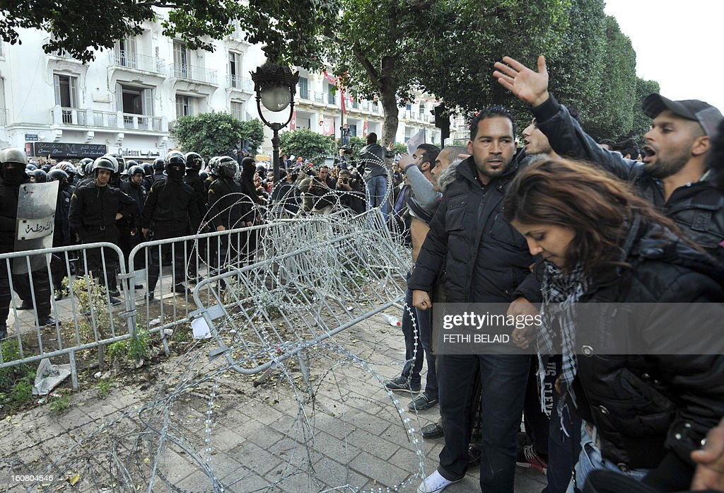 Tunisian protesters shout slogans in front of riot policemen during a rallye outside the Interior ministry to protest after Tunisian opposition leader and outspoken government critic Chokri Belaid was shot dead with three bullets fired from close range, on February 6, 2013 in Tunis. The protesters, who massed on Habib Bourguiba Avenue, epicentre of the 2011 uprising that ousted ex-dictator Zine El Abidine Ben Ali, pelted the police with bottles and the police responded by firing tear gas, chasing the protesters and beating them with batons.
