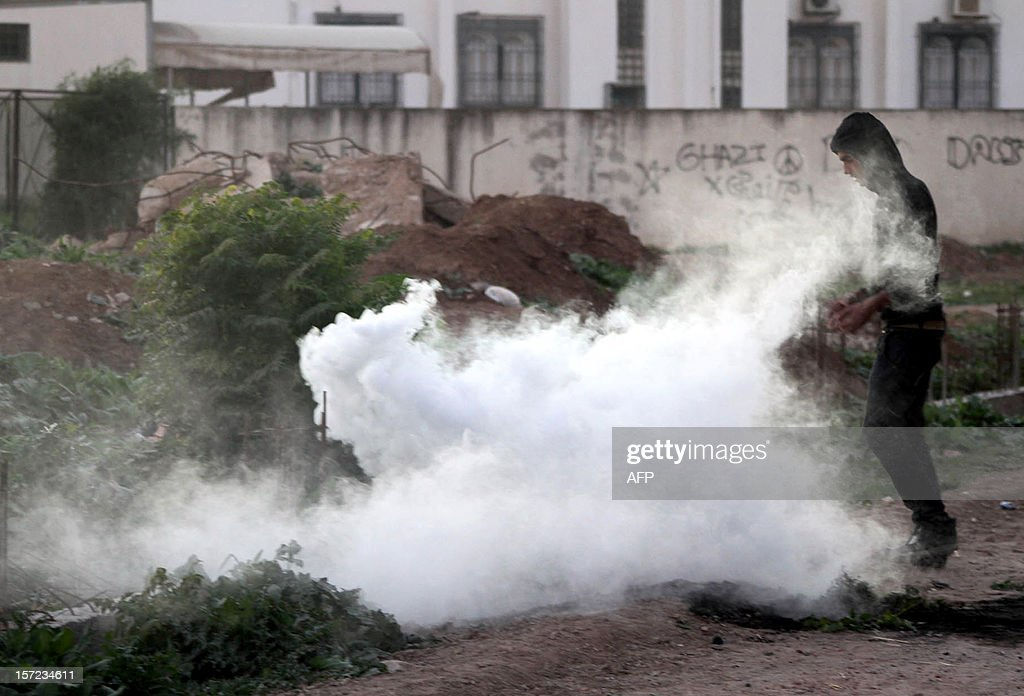 A Tunisian protestor stands next to a smoke grenade during clashes with security forces in the town of Siliana, 120 kilometres (75 miles) southwest of Tunis, following a demonstration on November 30, 2012. Protesters clashed with police in Tunisia's flashpoint town of Siliana, where violence has left hundreds wounded this week, as political instability mounts two years after the revolution.